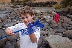 Urlopowej chłopiec chwytający krab przy rzeką Zdjęcia Royalty Free