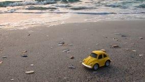 Urlopowy i podr?? poj?cie Jaskrawy mały retro zabawkarski samochód na piasku w tło falach morze, zbiory wideo