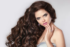 Сurly hair. Beautiful brunette woman model with makeup, fashion Stock Photos