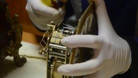 Urmakaren med vita handskar undersöker noggrant det mekaniska systemet av den antika klockpendelklockan arkivfilmer