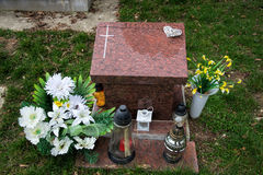 Urn grave with cross on traditional cemetery. Votive candles lantern and flowers on tomb stones in graveyard. All Saints' Day Stock Image