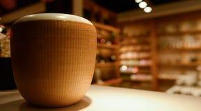 Urna de cerámica blanca con la chaqueta bambú-filamento-tejida en la tabla adentro fotografía de archivo