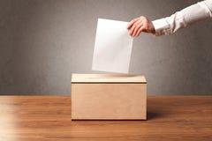 Urna de voto com voto de carcaça da pessoa Foto de Stock