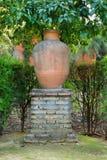 Urna del jardín en un soporte grande del ladrillo como característica decorativa Imagen de archivo libre de regalías