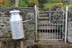 Urna del latte fuori di un cottage del paese immagini stock libere da diritti