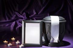 Urna negra del cementerio con las velas de luto negras del marco y cinta blanca en fondo de color morado oscuro Imagen de archivo