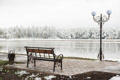 Urnbank en lantaarn op een achtergrond van een een de winterpark en meer stock foto's