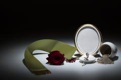 Urne blanche avec le cadre de deuil vide, la rose de rouge, la bande verte et le r Images stock