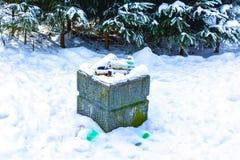 urne couverte de neige pour des déchets en parc d'hiver photos stock
