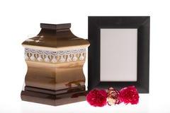 Urne en bois avec le cadre et la fleur de deuil vides Images stock