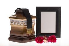 Urne en bois avec le cadre et la fleur de deuil vides Image stock