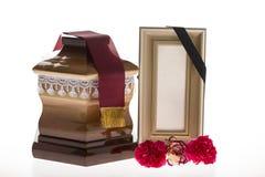 Urne en bois avec le cadre et la fleur de deuil vides Photographie stock