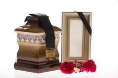 Urne en bois avec le cadre et la fleur de deuil vides Image libre de droits