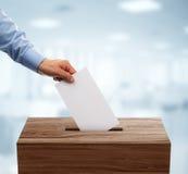 Urne en rouge, blanc, et le bleu avec le vote chutant dedans Photo stock