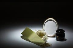 Urne noire avec la bande verte, rose de blanc, pour la carte de sympathie Photos stock