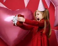 Urocza ładna dziewczyna z menchiami szybko się zwiększać i czerwieni teraźniejszy prezent i urodzinowa nakrętka Zdjęcie Royalty Free