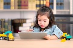 Urocza śliczna mała Azjatycka dziewczyna w cajgach shirtdrawing na biurku Co obraz stock