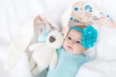 Urocza śliczna nowonarodzona dziewczynka z turkusową kwiat kapitałką z Wielkanocnym królikiem Obrazy Stock