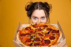 Urocza śliczna pozytywna młoda kobieta chuje za pizzą Obrazy Stock