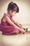 Urocza azjatykcia dziewczyna bawić się z blokami bawi się na podłoga Fotografia Royalty Free