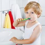 Urocza berbeć chłopiec szczotkuje jego zęby, indoors Obrazy Royalty Free