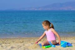 Urocza berbeć dziewczyna bawić się z jej zabawkami przy plażą Zdjęcie Stock