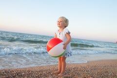 Urocza berbeć dziewczyna bawić się z piłką na piasek plaży Obraz Royalty Free