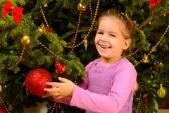 Urocza berbeć dziewczyna trzyma dekoracyjnych boże narodzenia bawi się piłkę fotografia royalty free
