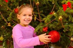Urocza berbeć dziewczyna trzyma dekoracyjnych boże narodzenia bawi się piłkę zdjęcie royalty free