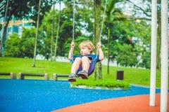 Urocza blond chłopiec na huśtawce w parku Urocza chłopiec ma zabawę przy boiskiem zdjęcia royalty free