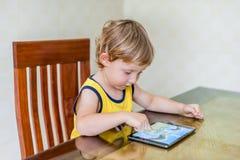 Urocza blondynka berbecia chłopiec bawić się z cyfrową pastylką zdjęcia stock