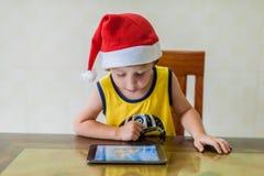 Urocza blondynka berbecia chłopiec bawić się z cyfrową pastylką Zdjęcia Royalty Free