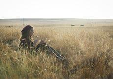 Urocza brunetki kobieta sadzająca w świetle słonecznym w polu obraz stock