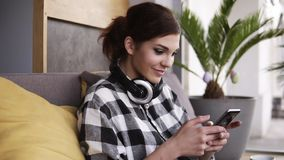 Urocza brunetki kobieta siedzi na kanapie z żółtą poduszką Mienie telefon komórkowy w rękach, scrolling i ono uśmiecha się, _ zdjęcie wideo
