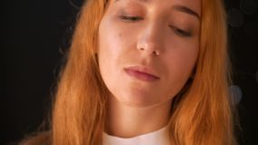 Urocza caucasian imbirowa kobieta jest przyglądającym kamerą prosto i wtedy na boku spogląda w czarnym studia zakończeniu podczas