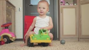 Urocza chłopiec bawić się z dużą samochód zabawką na podłodze w domu Żartuje chłopiec berbecia bawić się z zabawkarskim samochode zbiory wideo