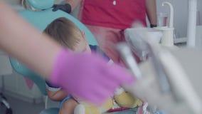 Urocza chłopiec bawić się z medycznymi narzędziami siedzi w krześle w dentysty biurze Beztroski dziecka odwiedzać zbiory