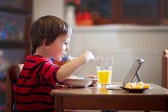 Urocza chłopiec, je jego kolację, podczas gdy oglądający film fotografia royalty free