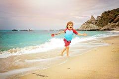 Urocza chłopiec ma zabawę przy plażą na wakacje Żartuje być ubranym pływackich bagażniki i słońca ochrona strzelającego bawić się zdjęcia stock