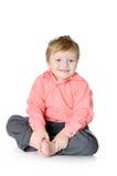 Urocza chłopiec ono uśmiecha się, siedzący na podłoga, zdjęcia royalty free