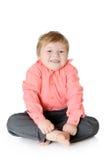 Urocza chłopiec ono uśmiecha się, siedzący na podłoga, obrazy stock