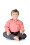 Urocza chłopiec ono uśmiecha się, siedzący na podłoga, obraz royalty free