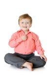 Urocza chłopiec ono uśmiecha się, siedzący na podłoga, obraz stock