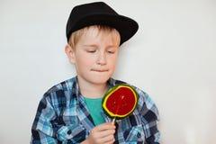 Urocza chłopiec patrzeje dużego kolorowego lizaka w modnej koszula i czarnej nakrętce Śliczny uczeń jest ubranym modnych ubrań ki obrazy stock