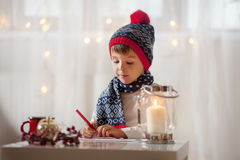 Urocza chłopiec, pisze liście Santa obraz stock