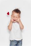 Urocza chłopiec pozuje z małym papierowym sercem Miłość obrazy stock