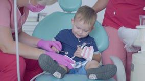 Urocza chłopiec w dentysty biurze bawić się z szczęka egzaminem próbnym Beztroski dziecko odwiedza lekarkę leczenie dentystyczne zdjęcie wideo
