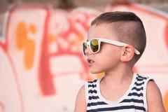 Urocza chłopiec z okularami przeciwsłonecznymi i żeglarzów lampasami przekazuje na graffiti tle Zdjęcie Royalty Free