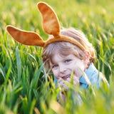 Urocza chłopiec z Wielkanocnego królika ucho bawić się w zielonych gras Obrazy Stock