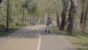 Urocza ch?opiec w jaskrawym odziewa rollerblading w parku blisko rzeki Czas wolny outdoors Dzieciak ma zabaw? samotnie zdjęcie wideo